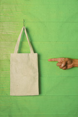hand and finger pointing to clothes bag on green background