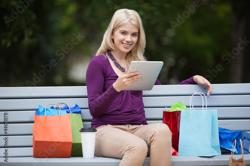 Woman With Shopping Bags Using Tablet PC Outdoors