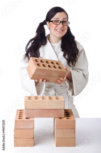 Woman karate breaking bricks on white
