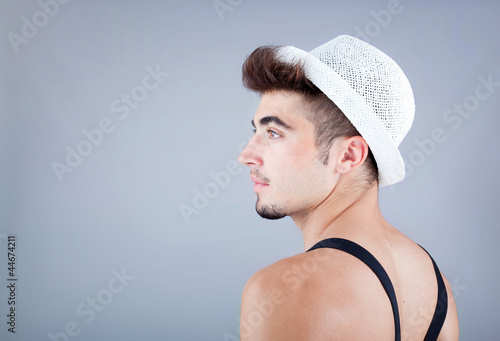 Portrait of a handsome young man in hat against grey background