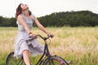 Pretty young woman riding bike in a country road.
