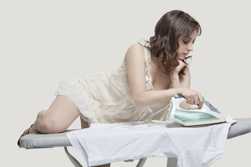 Young woman comfortably ironing shirt against gray background