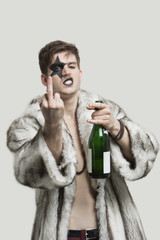 Portrait of young man with a rude gesture while holding beer bottle against gray background