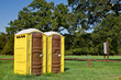 Two yellow portable toilets at a park