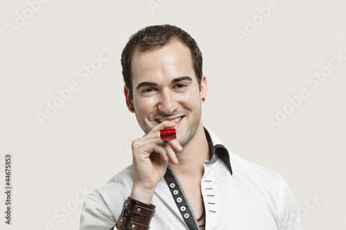 Portrait of young man blowing party puffer against gray background