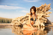 Beautiful brunette posing on river bank. Art photo.