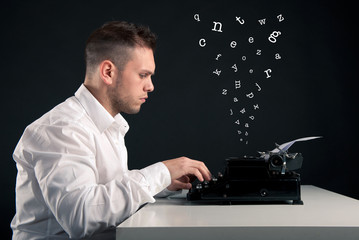 Young man writing with an old typewriter. Conceptual image
