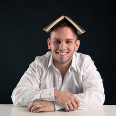 Young man playing with a book as a hat against black background.