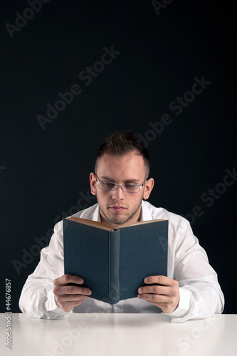 Young man reading a book against black background.