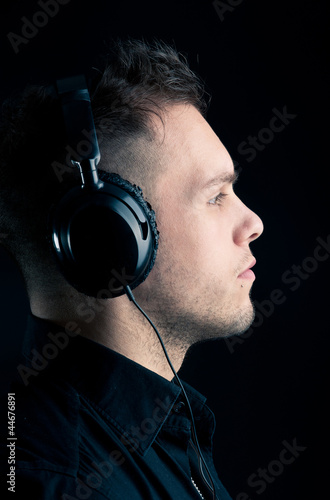Close up profile of man with ear-phones on black background.
