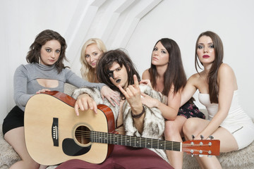 Young male guitarist with cool gesture surrounded by female friends