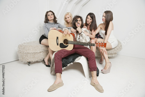 Portrait of young male guitarist sitting amid young female friends
