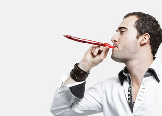 Young man blowing party blower against gray background