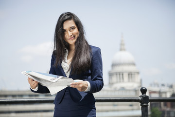 Portrait of Indian businesswoman holding newspaper with St. Paul's Cathedral in background