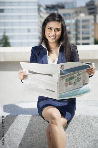 Portrait of a smart Indian businesswoman holding newspaper as she sits outdoors