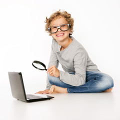schlauer Junge sucht mit Lupe am Computer