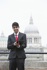 Portrait of a happy Indian businessman using tablet PC against St. Paul's Cathedral