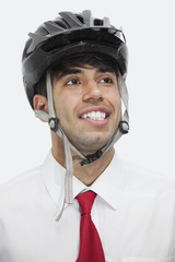 Young Indian businessman wearing cycling helmet while looking away against gray background