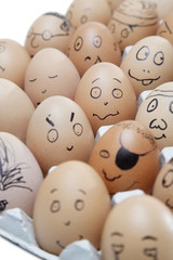 Anthropomorphic brown eggs arranged in carton against white background