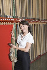 Portrait of pretty businesswoman holding thin veneer sheet and samples