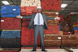Portrait of happy African American male engineer standing with arms outstretched in front of stacked wooden planks