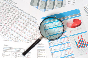 magnifying glass over financial reports