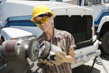 Female industrial worker buffing a truck engine cylinder