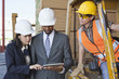 Engineers and female industrial worker looking at tablet PC