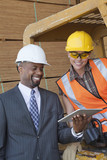 African American businessman and female industrial worker looking at tablet PC