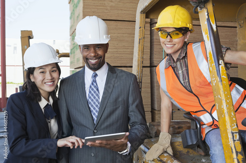 Portrait of engineers and female industrial worker smiling