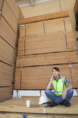 Pensive female industrial worker sitting cross-legged on wooden planks