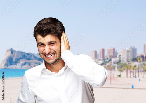 portrait of irritated young man hearing a loud against a beach