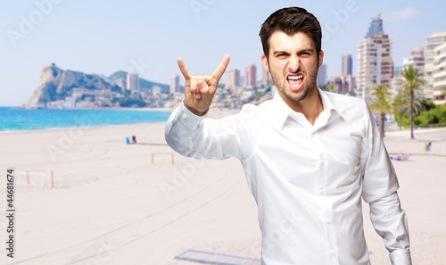 portrait of young man doing rock symbol against a beach