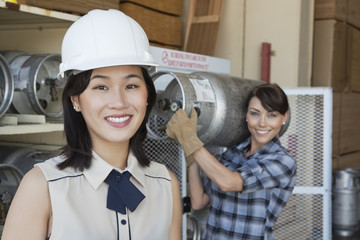 Portrait of woman smiling with female industrial worker carrying propane cylinder in background