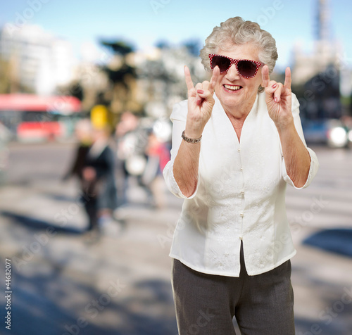portrait of a happy senior woman doing rock symbol at crowded st