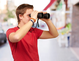 portrait of young man looking through a binoculars at street