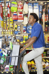 Side view of African American man with shopping cart at hardware store