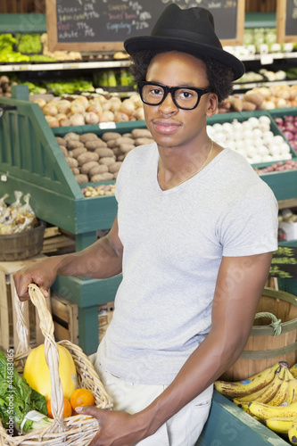 Portrait of an African American man with vegetable basket at supermarket