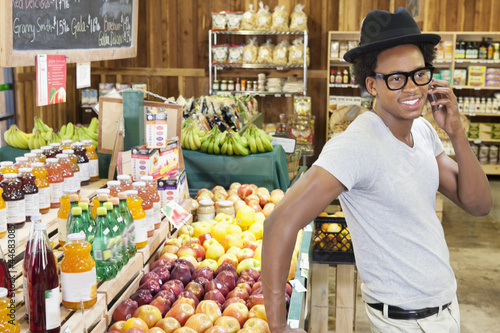 African American man using cellphone at supermarket