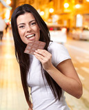 portrait of young woman eating chocolate bar at night city