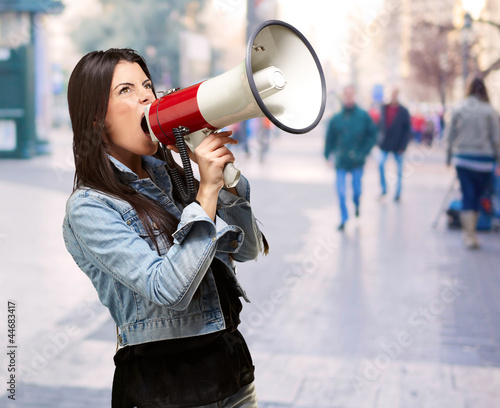 portrait of young woman screaming with megaphone at crowded stre