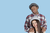 Bored African American man with smiling girlfriend over blue background