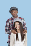 Portrait of happy multi ethnic couple over blue background