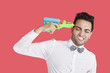 Frustrated man holding toy gun to his head over red background