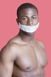 Portrait of shirtless African American man with tape over mouth against pink background