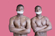 Portrait of two muscular African American men with tapes covering mouth over pink background