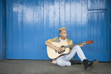 Trendy teenage boy playing guitar as he sits against wood paneled wall
