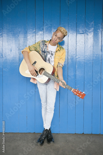 Portrait of a trendy teenage boy playing guitar against wood paneled wall