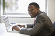Portrait of happy African American businessman using laptop at office desk
