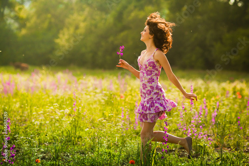 Beautiful young woman running in purple flowers outdoors